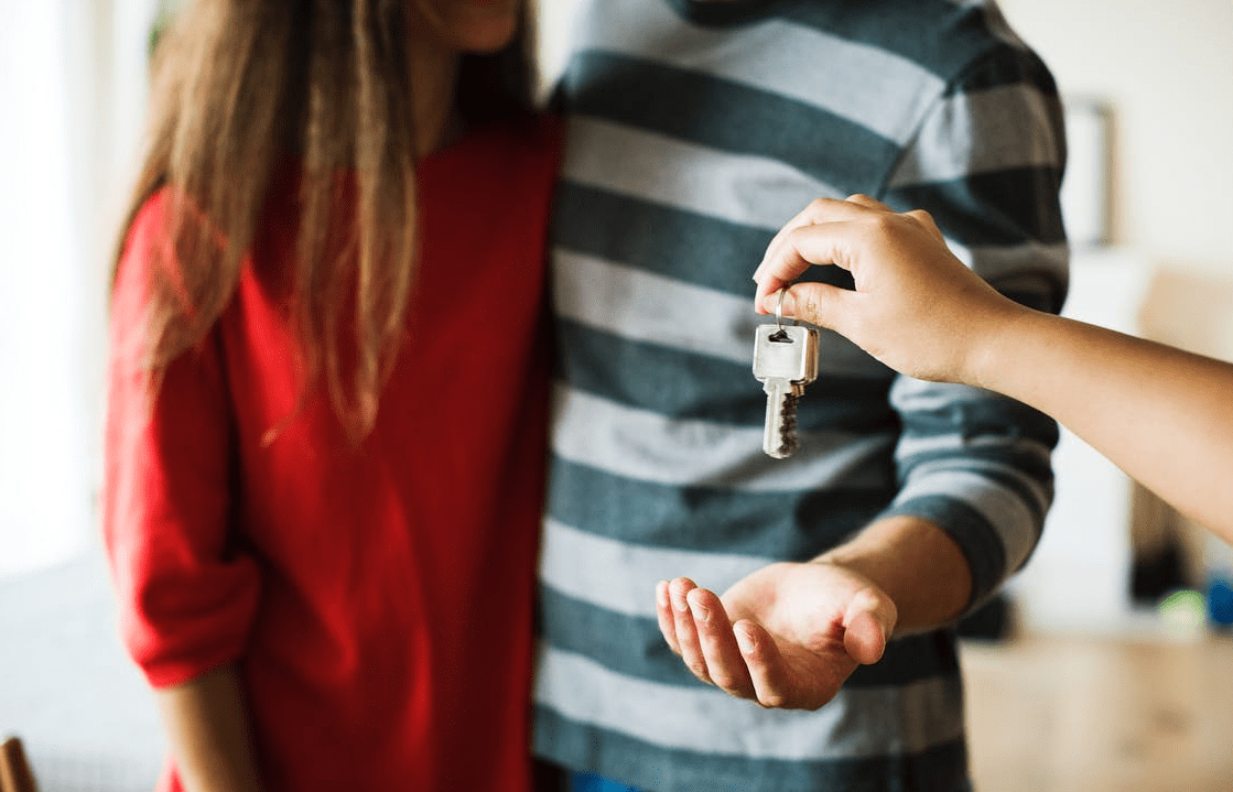 Image of a couple receiving keys to a property.