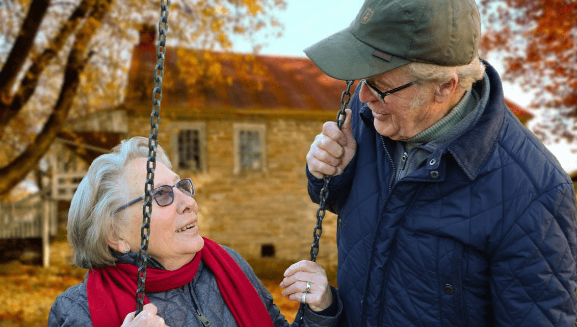 Image of two elderly people by a swing.