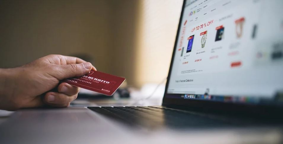Image of a person holding a credit card for e-commerce.