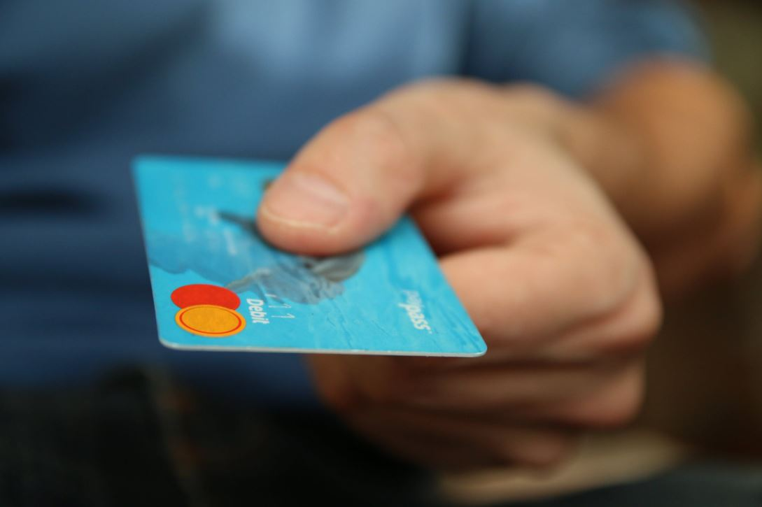 Large image of a person holding a debit card.
