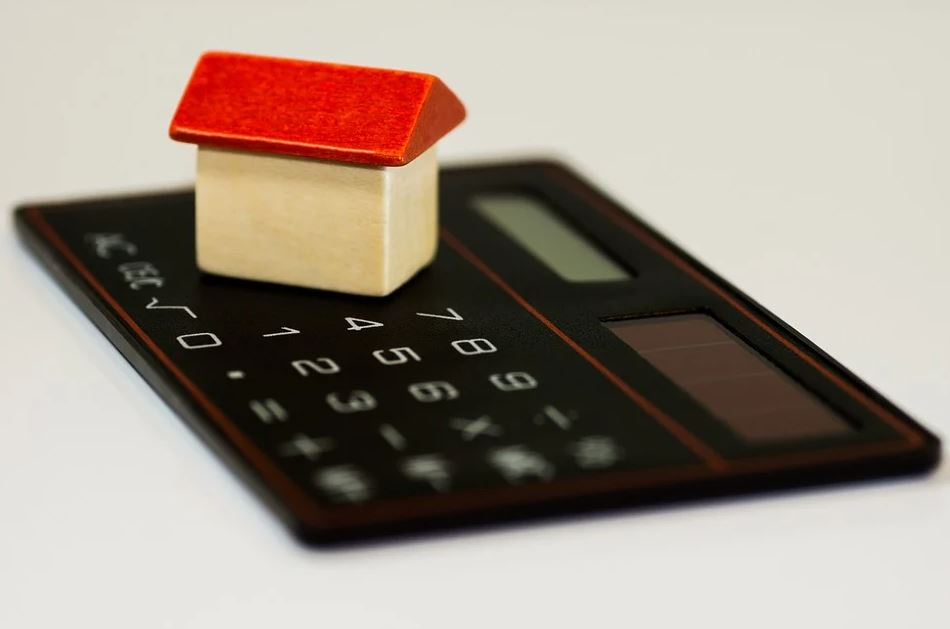 Image of a house on top of a calculator.