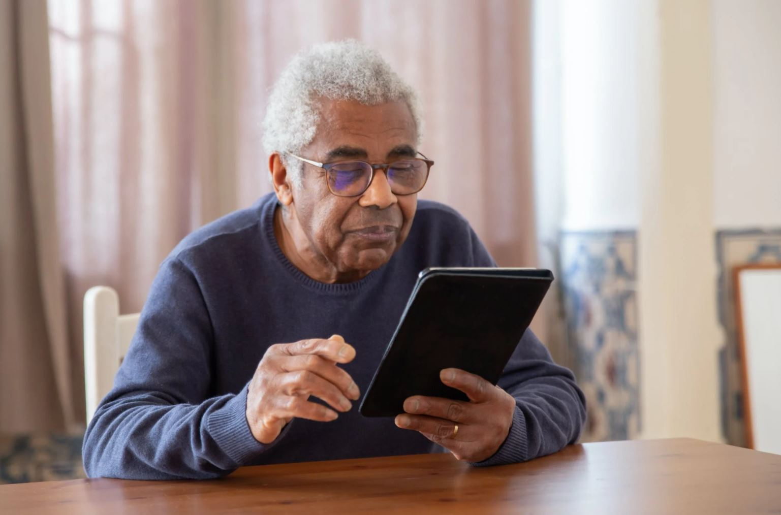 Image of an elderly man on a tablet device.